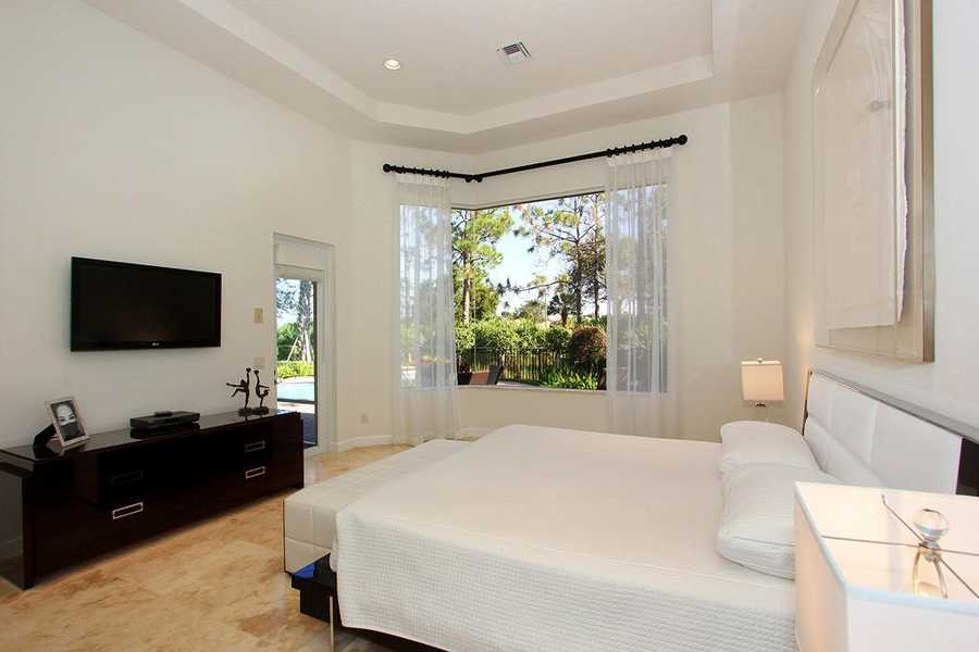Ground floor master suite, with a large golf course-facing window and private access to the pool area.