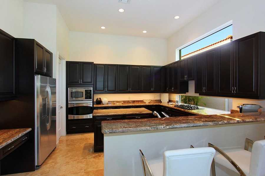 Spectacular kitchen boasts custom cabinetry, stainless steel appliances, and a marble topped cooking island.