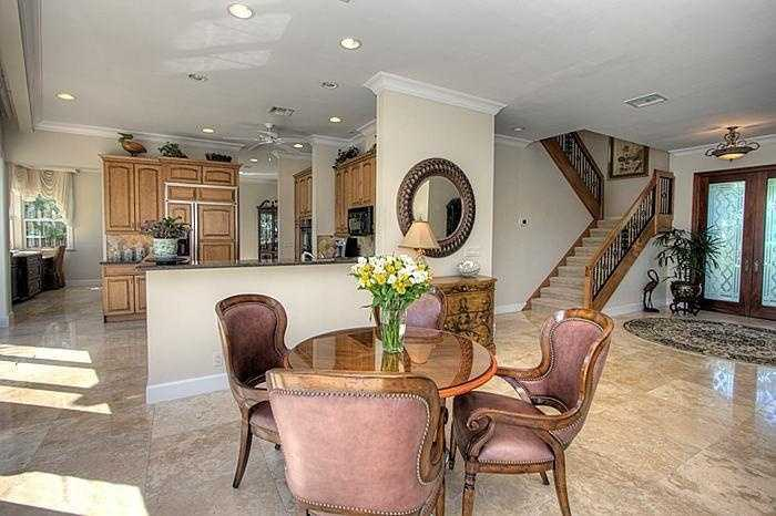 This space between the kitchen and living room is occupied by an antique dining set.