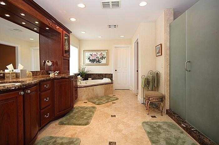 Master bathroom boasts a generous dual vanity, spa bath, and shower.