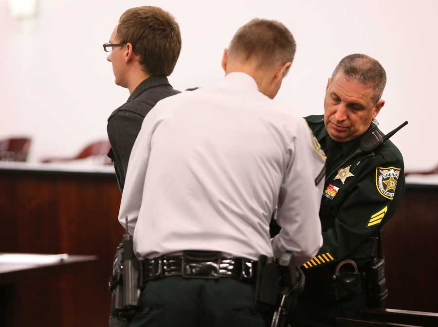 "Travis Van Vliet, ""Juror 100"", is taken into custody for contempt of court and handcuffed. He was reportedly overhead talking about a 'retrial' in the hall Thursday, October 9, 2014 during jury selection in Tampa. (Photo credit: Lannis Waters / The Palm Beach Post)"