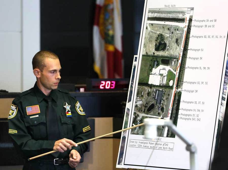 Robert Stephan, a traffic homicide investigator with PBSO, points out the path he followed of John Goodman's footprints to the driveway to Lisa Pembleton's trailer as he testifies on the fifth day of John Goodman's retrial Thursday, October 16, 2014. Goodman is charged with DUI manslaughter in the death of Scott Wilson. (Lannis Waters / The Palm Beach Post)