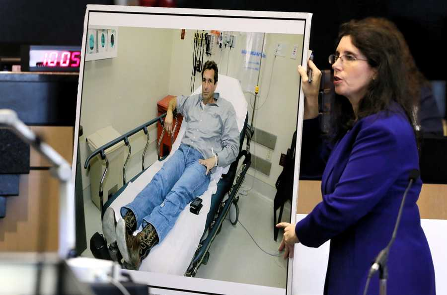 Prosecutor Sherri Collins shows investigator Troy Snelgrove a photo taken of John Goodman in the hospital, showing his boots, as she questions Snelgrove on the sixth day of Goodman's retrial Friday, October 17, 2014. There had previously been testimony without the jurors present about the release of Goodman's Bentley. Goodman is charged with DUI manslaughter in the death of Scott Wilson. (Lannis Waters / The Palm Beach Post)
