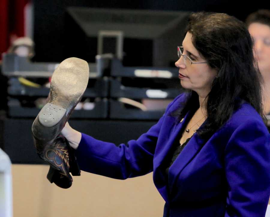 Prosecutor Sherri Collins shows the bottom of John Goodman's boot to investigator Troy Snelgrove as he testifies on the sixth day of Goodman's retrial Friday, October 17, 2014. There had previously been testimony without the jurors present about the release of Goodman's Bentley. Goodman is charged with DUI manslaughter in the death of Scott Wilson. (Lannis Waters / The Palm Beach Post)