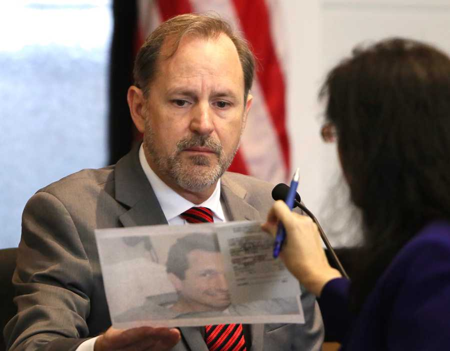 Dr. Stephen Alex is shown a photo of John Goodman, taken the night of the accident, by prosecutor Sherri Collins as they discuss the size of the cut in his forehead during the tenth day of Goodman's retrial Wednesday, October 22, 2014. Goodman is charged with DUI manslaughter in the death of Scott Wilson. (Lannis Waters / The Palm Beach Post)