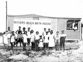 Beach-goers assembled for a group portrait by the bath house at Butler Beach in Anastasia Island, Florida. This was the only beach African Americans were allowed to use between Jacksonville and Daytona Beach.