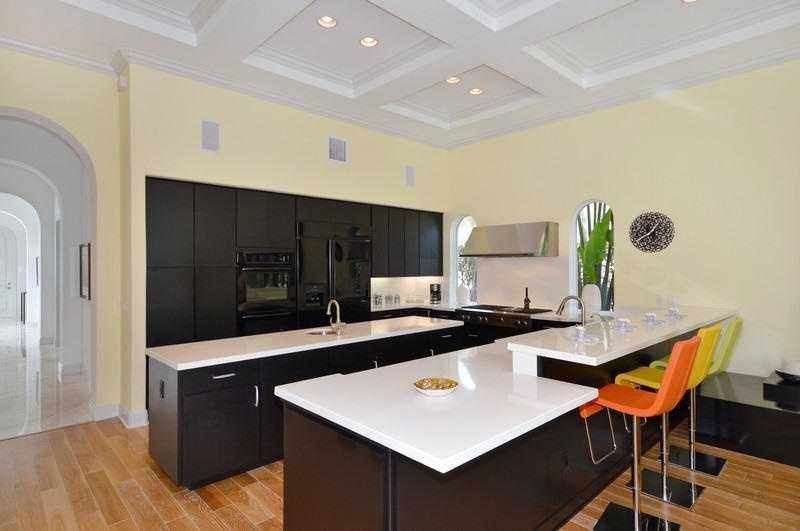 This custom kitchen features recessed lighting, sleek cabinetry, a center island, two sinks, and immense counter space.