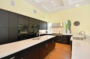Sleek dark cabinets create a stylish contrast with lighter hardwood floors.