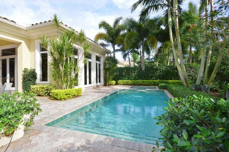 Sparkling pool is surrounded by lush landscaping for privacy.