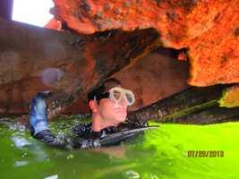 DERM diver Felix Alvarez examines large hole in barge's forward rank.
