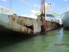 Port side of hull with holes and plywood patches.
