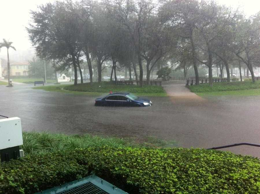 A car gets stuck in the water behind Phillips Point in downtown West Palm Beach.
