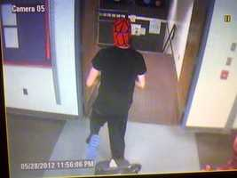 Brandon Beliveau, wearing a Spiderman mask, duct tapes over Milton Middle/High School's security cameras.