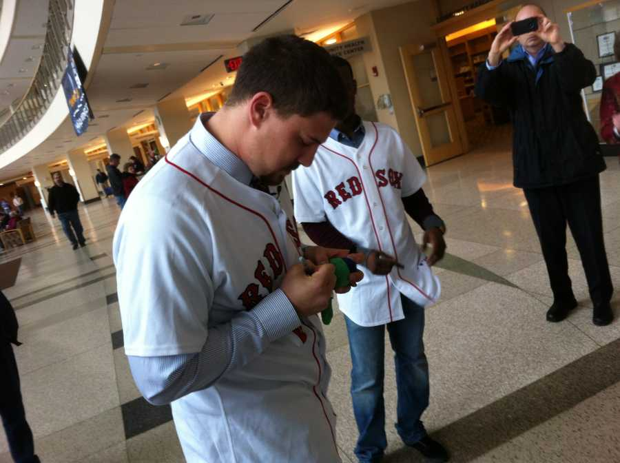 Ryan Lavarnway signs a Wally the Green Monster.