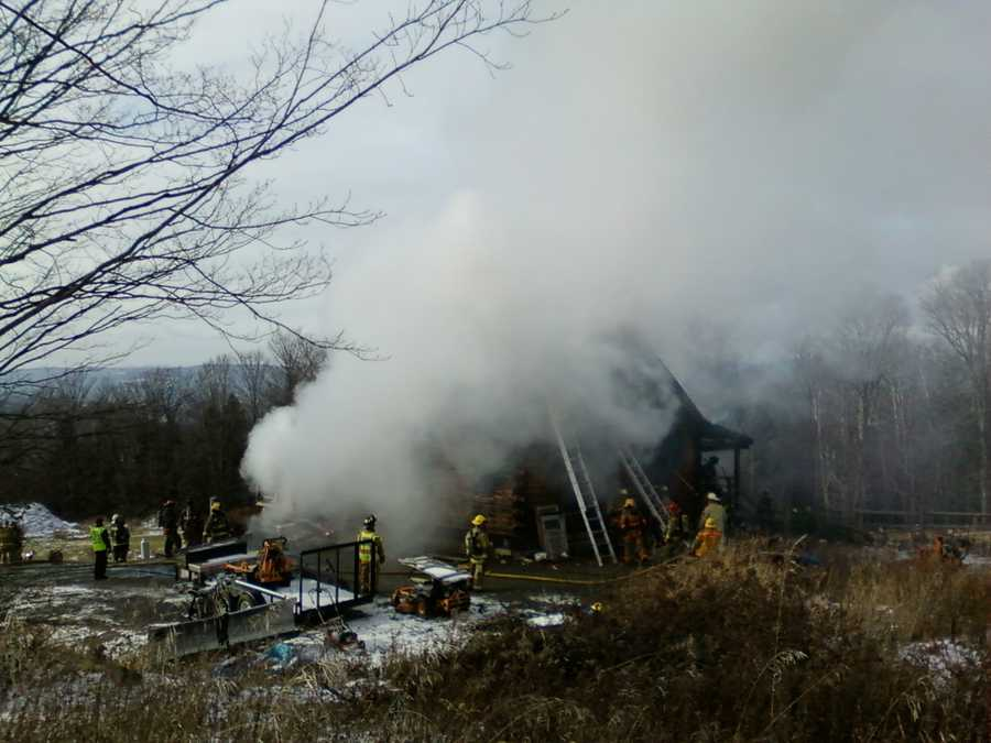 A log cabin on Phelps Road in Barre smolders and smokes after a fire tears through the home.