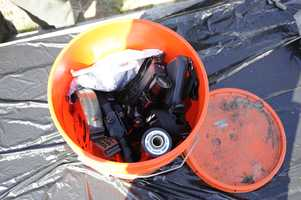 Inside the bucket: a silencer, a trigger mechanism with a scope attached&#x3B; .22 caliber Ruger minus stock&#x3B; plastic stock with sling, empty magazines&#x3B; fasteners, ammunition, wires, a metal clip and a flashlight.