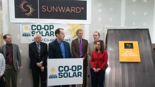 Sunward Systems CEO Tom Hughes inside the company's Shelburne factory with other state leaders promoting the 2013 Co-op Solar Hot Water program.