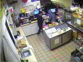 The suspect is seen taking money from the register.