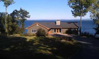 This is a must-see to believe lakefront cliff side retreat with spectacular mountain views. Fall asleep to the sound of waves crashing on the rocky shore and be mesmerized by the breathtaking sunrises. This home is located in the desirable and private Woodcliff community just outside the city limits. Gorgeous Cherry Brazilian hardwood floors, as well as Red Tiger Maple. The kitchen features beautiful granite countertops and a Woodmode kitchen with major appliances having been updated. This home has two levels of deck space with a state-of-the-art outdoor kitchen. Information from listing.
