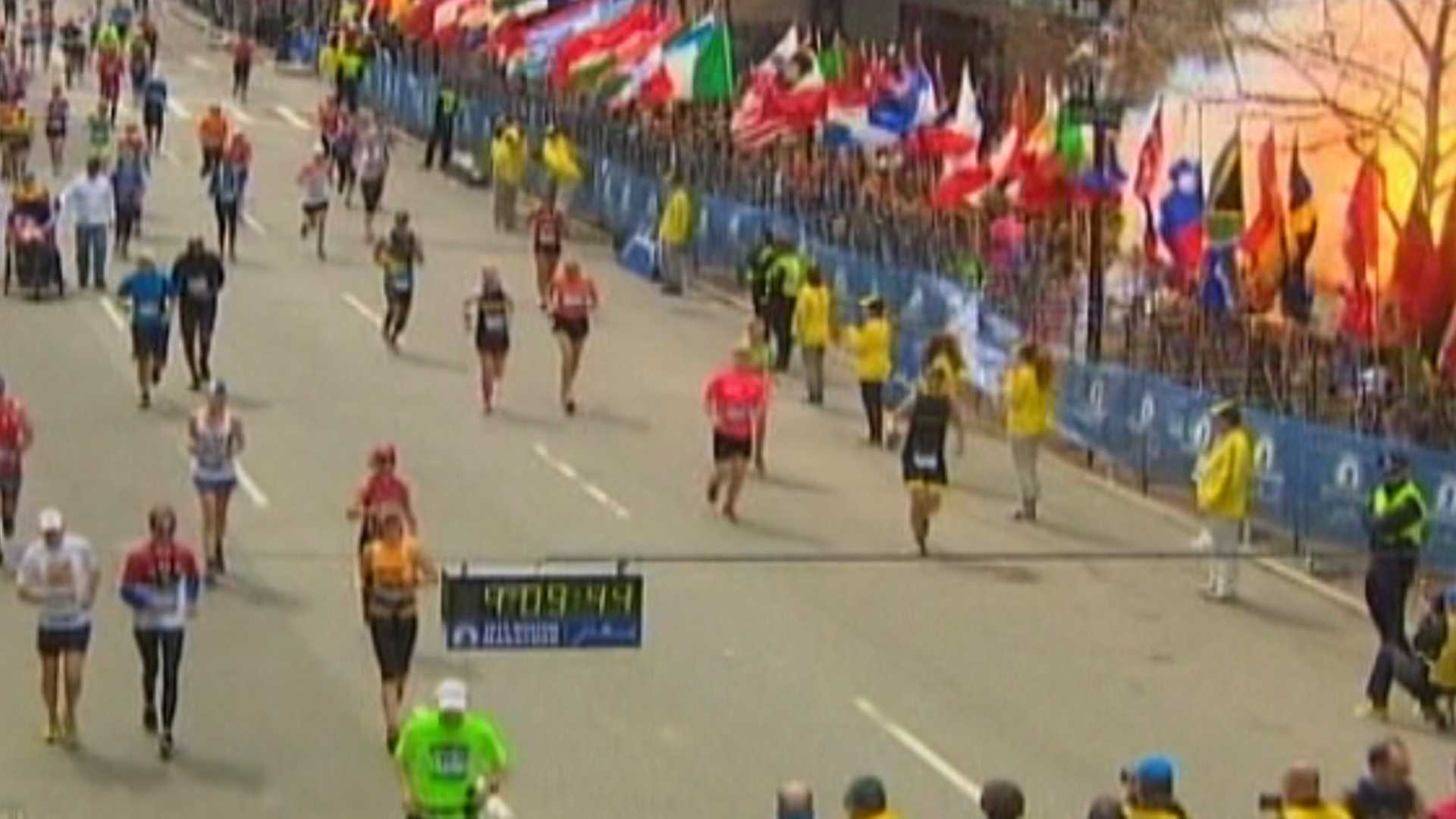 A bomb explodes at the finish line of the Boston Marathon. You can see a fireball at the top-right corner of the photo.