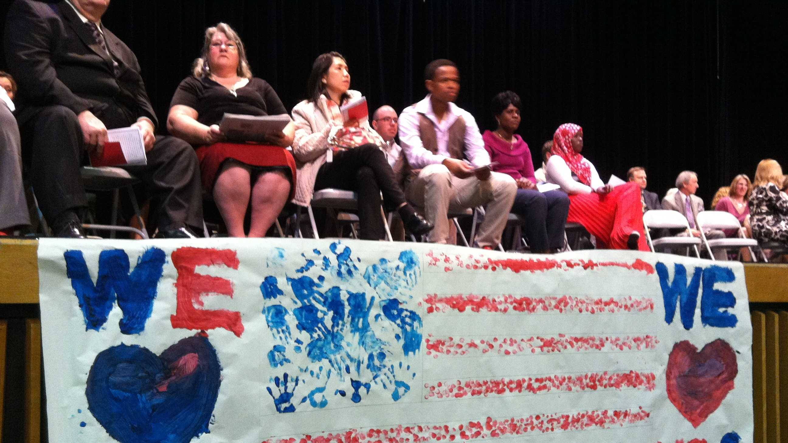 New Americans prepare to take their oath of allegiance at Essex Junction High School.