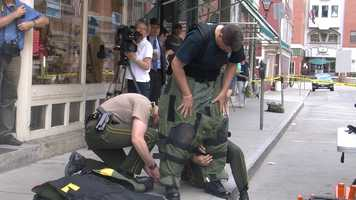 A bomb squad officer suits up.