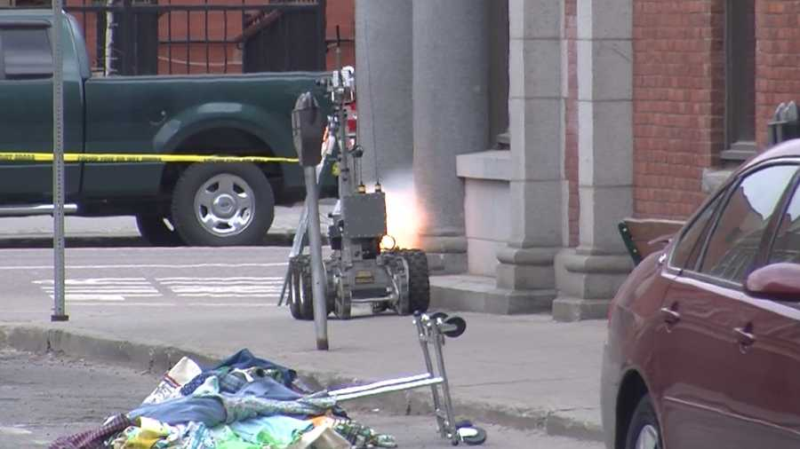 The bomb squad explodes the cardboard box. To do it, they fire pressurized water.