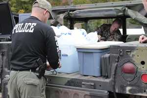 Chief David Kratz of the Danbury Police Department helps Spencer Marvin, Cruelty Investigation Officer and Field Services Manager at UVHS, load a Humvee with clean water. UVHS carted 50 gallons of clean water up the mountain each day.