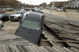 Pedestrians walk past the boardwalk and cars displaced by superstorm Sandy, near Rockaway Beach in the New York City borough of Queens, Tuesday, Oct. 30, 2012, in New York.