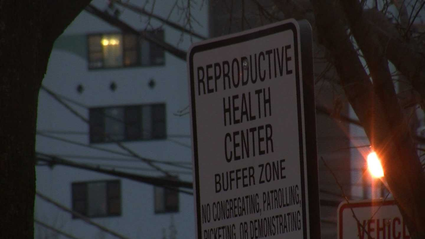A traffic court hearing officer rules in favor of the City of Burlington after a complaint is filed against a woman who the city says violated a buffer zone ordinance by placing anti-abortion stickers on her car.