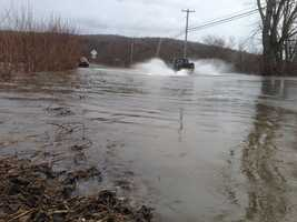 A truck splashes through the Lamoille River flood waters covering Route 15 in Cambridge, Vt.