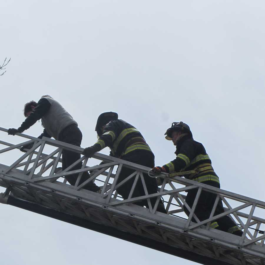 Emergency crews work to rescue a pilot caught in a tree after parachuting out before the plane crashed on Interstate 89N in Highgate, Vt.