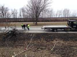 Crews examine the burned out wreckage of the small plane that crashed Friday afternoon on Interstate 89N in Highgate, Vt. The pilot sustained minor injuries after parachuting to safety.