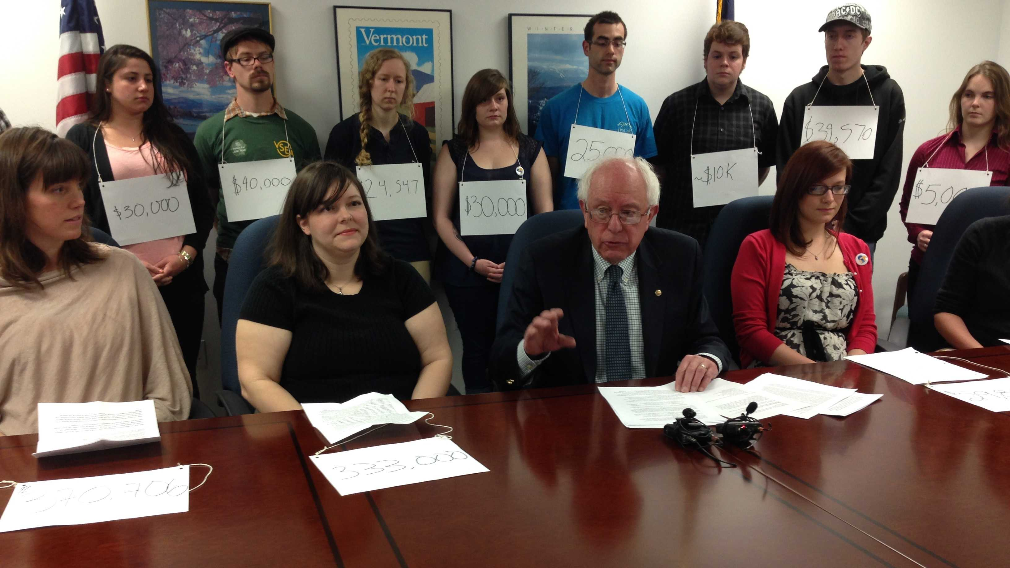 U.S. Senator Bernie Sanders is surrounded by Vermont college students wearing signs noting their debt load.