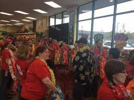 Trader Joe's employees pass out leis to shoppers on opening day.