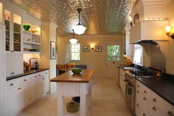 Renewed kitchen boasts stainless steel appliances, bold tin ceilings, and a beautiful center island.