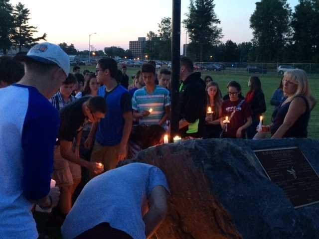 Bringing candles to the memorial rock on campus.