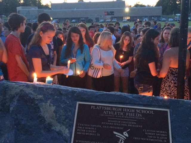 Plattsburgh High School students bring candles to a memorial rock on campus