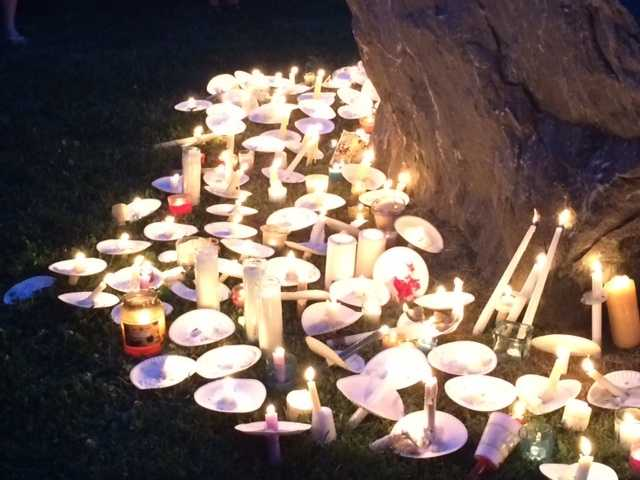Candles flicker for Taoufik Maknani, 17 and Mike Lawson.