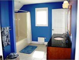 One of the en suite bathroom is spacious and features a tub.