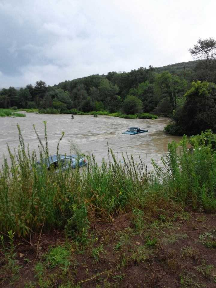 Two vehicles stuck in a flooded cornfield in Chester, Vt.