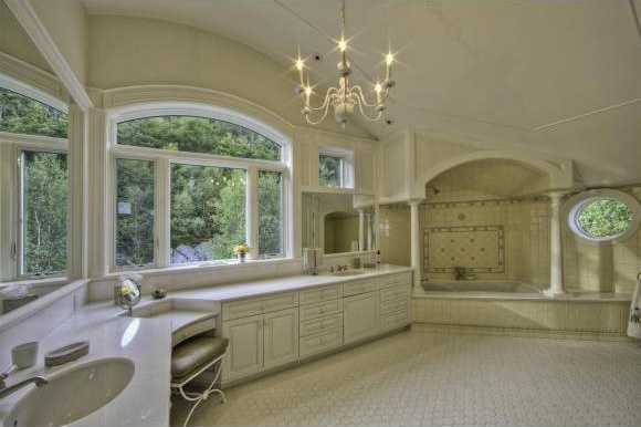 This sophisticated en suite bathroom also features a spa tub and idyllic chandelier.