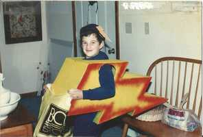 Meteorologist John Hickey was destined to be where he is today from in early age. Just check out his costume at age 7. He's 'Lightning Bolt Man'. His dad created the lightning bolt by cutting armholes in a cardboard box then spray painted it. Also note the cool lightning bolt on his backwards hat.