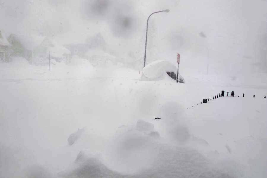 A 4-foot fence and SUV are nearly buried along a street in Buffalo, N.Y. on Tuesday, Nov. 18, 2014. Parts of New York measured the season's first big snowfall in feet, rather than inches, as 3 feet of lake-effect snow blanketed the Buffalo area. The Thruway Authority said white-out conditions caused by wind gusts of more than 30 mph forced the closure of Interstate 90 in both directions from the Rochester area to Ripley, on the Pennsylvania border 60 miles southwest of Buffalo.