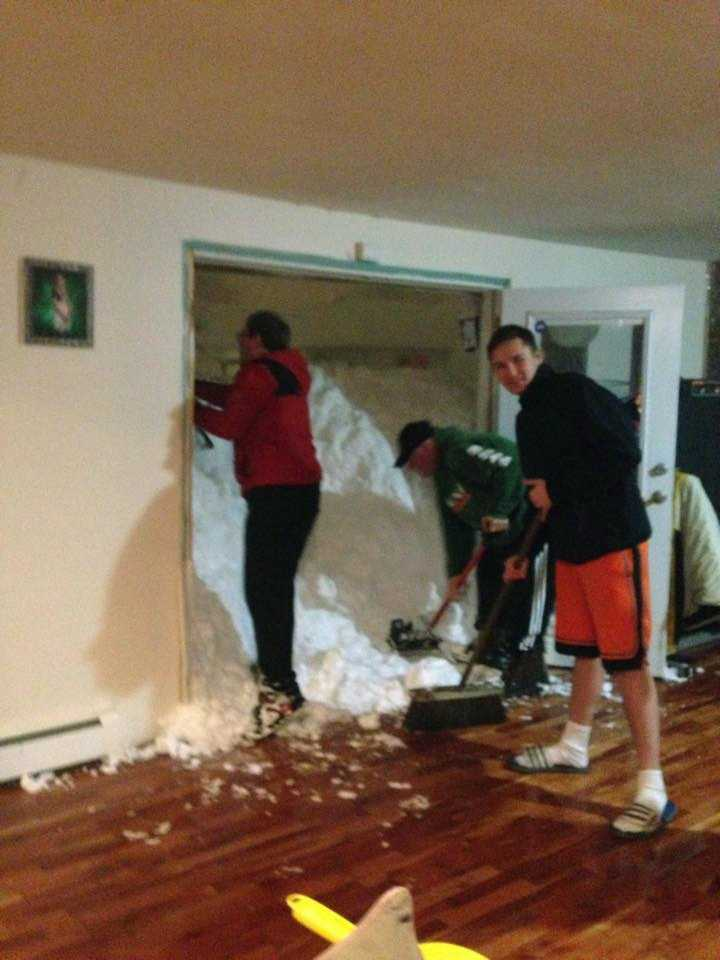 In this photo provided by Chrissy Hazard, Mark Hazard, his son Jason and Bryan Juda shovel out the snow from the home of Chrissy Hazard on Tuesday, Nov. 18, 2014 in Cheektowaga, N.Y.