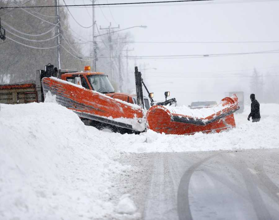 A plow truck clears an opening from a side street on Wednesday, Nov. 19, 2014, in Lancaster, N.Y.