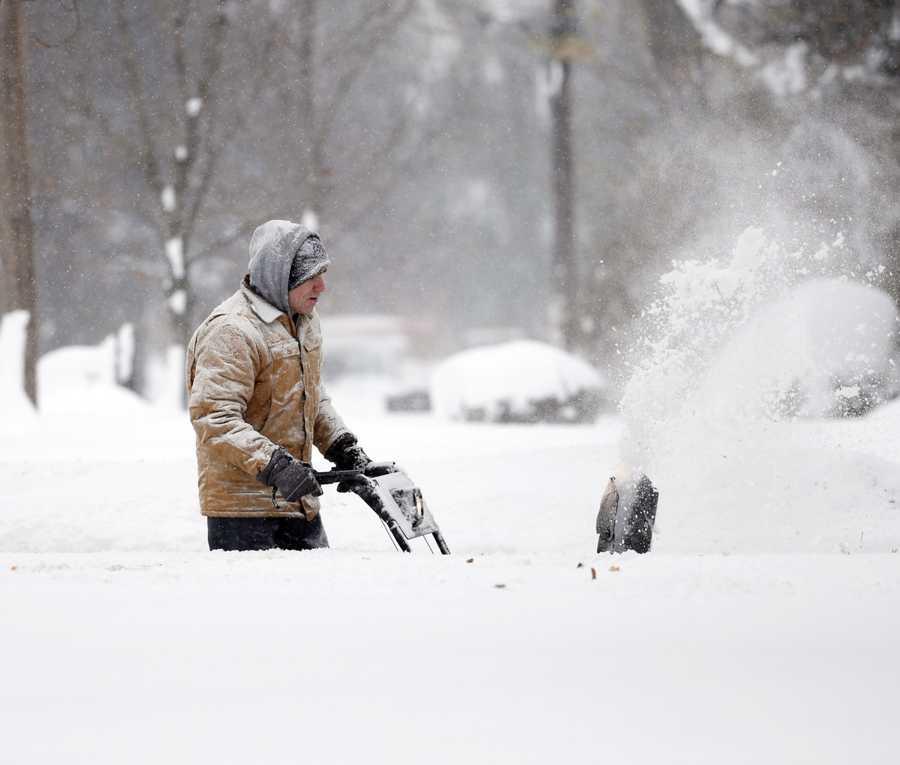 Ken Velie clears snow from his driveway on Wednesday, Nov. 19, 2014, in Lancaster, N.Y.