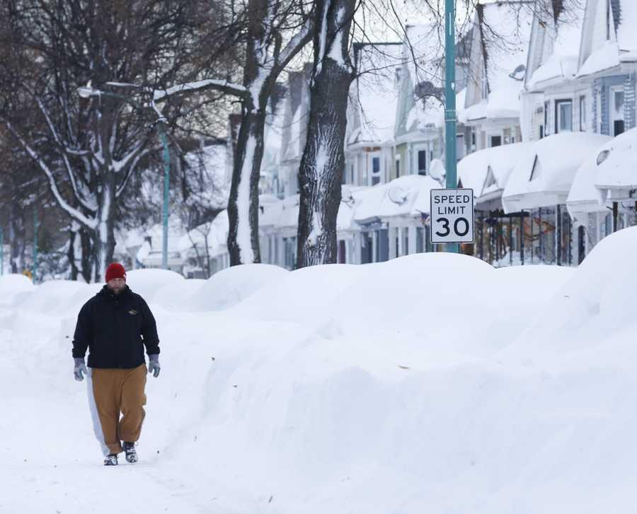 Chris Weiglein walks along his snow-bound south Buffalo neighborhood on Thursday, Nov. 20, 2014, in Buffalo, N.Y.