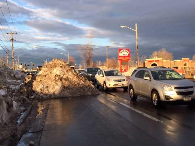A snow pile blocks one lane of traffic on Seneca Street.