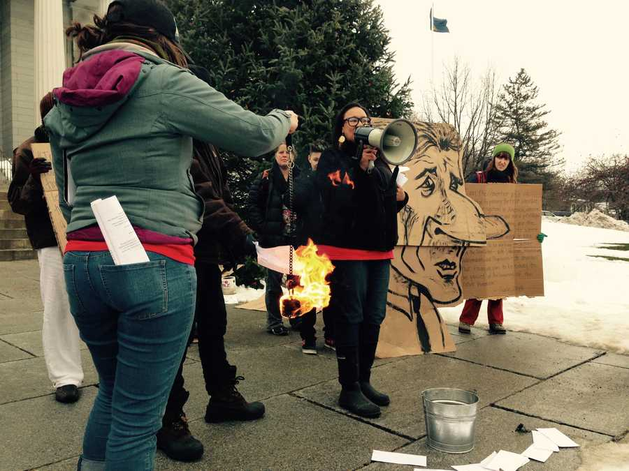 Protestors burn medical bills on the Statehouse lawn.